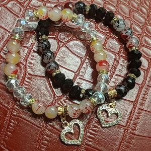 Two beaded bracelets with charms
